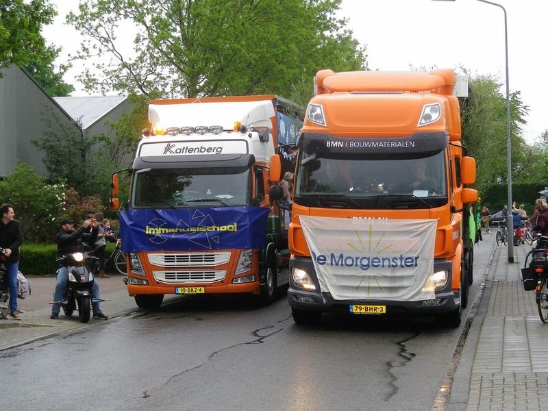 twee vrachtwagens versierd koningsdag school